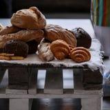 Verschillend soort brood bij wit servet op houten pallet stock afbeeldingen