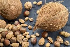 Verschillend soort van noten op een zwarte leisteen Een heerlijke snack stock foto