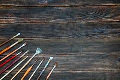 Verschillende borstels aan verf op donkere houten achtergrond, hoogste mening Royalty-vrije Stock Foto's