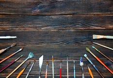 Verschillende borstels aan verf op donkere houten achtergrond, hoogste mening Stock Afbeelding