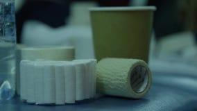 Verschillende broodjes van medisch verbanden en zorgmateriaal op een zwarte achtergrond Medische verbandbroodjes, elastisch verba stock videobeelden