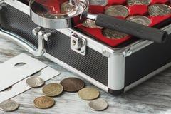 Verschillende collector` s muntstukken in de doos met een vergrootglas royalty-vrije stock afbeelding