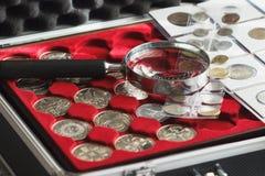 Verschillende collector` s muntstukken in de doos met een vergrootglas stock foto's