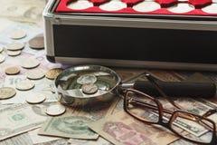 Verschillende collector` s muntstukken in de doos met een vergrootglas royalty-vrije stock fotografie