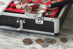 Verschillende collector` s muntstukken in de doos met een vergrootglas stock afbeelding