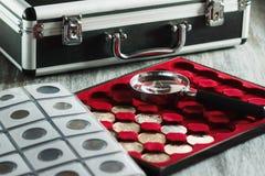 Verschillende collector` s muntstukken in de doos voor muntstukken en een vergrootglas stock foto