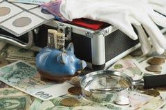 Verschillende collector` s muntstukken en bankbiljetten in de doos met stock fotografie