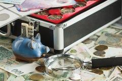Verschillende collector` s muntstukken en bankbiljetten in de doos, met een vergrootglas en een spaarvarken stock afbeeldingen