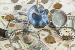 Verschillende collector` s muntstukken en bankbiljetten met een spaarvarken en een klok stock afbeeldingen