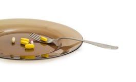 Verschillende dieetsupplementen op de donkere glasschotel met vork Stock Afbeeldingen