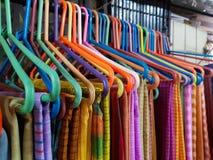 Verschillende gekleurde sarees op hangaar voor verkoop stock afbeeldingen