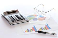 Verschillende grafieken met calculator en glazen royalty-vrije stock afbeelding