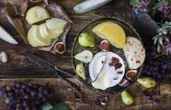 Verschillende kaas, verse vruchten en tuinbloemen op oude houten achtergrond Royalty-vrije Stock Afbeeldingen