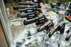 Verschillende kanonnen en revolvers op de wapens van de plankenopslag op winkelce stock afbeeldingen