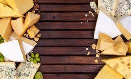 Verschillende kazen op houten lijst met lege ruimte Cheddar, parmezaanse kaas, emmentaler, blukaas Hoogste mening, exemplaarruimt royalty-vrije stock foto's