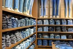 Verschillende keurig gevouwen jeans op de planken van de opslag in de Wandelgalerij royalty-vrije stock fotografie