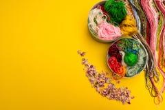 Verschillende kleuren van draad en bloemblaadjes op een gele achtergrond stock foto's