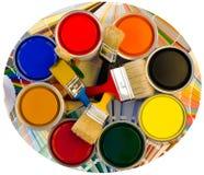 Verschillende kleurenblikken van verf en borstels op monstersachtergrond. Stock Fotografie