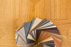 Verschillende kleurensteekproeven van houten vloer op bruine parketachtergrond. Royalty-vrije Stock Foto's
