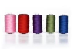 Verschillende kleurrijke die spoelen met het naaien van garen op een rij op witte achtergrond wordt geïsoleerd stock afbeelding