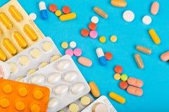 Verschillende kleurrijke pillen en plastic die pakken - blaren op blauwe abackground worden gestapeld royalty-vrije stock fotografie