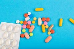 Verschillende kleurrijke pillen en plastic die pakken - blaren op blauwe abackground worden gestapeld stock fotografie
