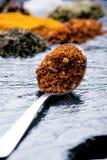 Verschillende kruiden en kruiden op een zwarte lei Ijzerlepel met Spaanse peperpeper Indische kruiden Ingrediënten voor het koken Stock Foto's