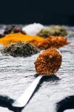 Verschillende kruiden en kruiden op een zwarte lei Ijzerlepel met Spaanse peperpeper Indische kruiden Ingrediënten voor het koken Royalty-vrije Stock Foto's