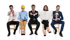 Verschillende mensen die op stoelen en elk doend iets anders zitten royalty-vrije stock afbeelding