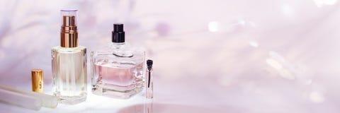 Verschillende parfumflessen en monstertrekker op een roze bloemenachtergrond Parfumerieinzameling, schoonheidsmiddelenbanner stock foto