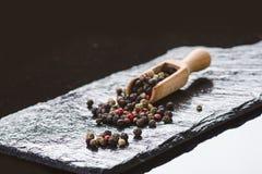 Verschillende peperkruiden op een zwarte lei Ingrediënten voor het koken Gezond het Eten Concept Diverse kruiden op donkere achte Royalty-vrije Stock Foto