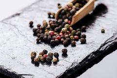 Verschillende peperkruiden op een zwarte lei Ingrediënten voor het koken Gezond het Eten Concept Diverse kruiden op donkere achte Royalty-vrije Stock Afbeelding