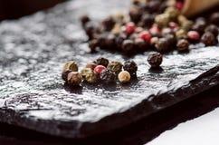 Verschillende peperkruiden op een zwarte lei Ingrediënten voor het koken Gezond het Eten Concept Diverse kruiden op donkere achte Royalty-vrije Stock Afbeeldingen