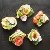 Verschillende sandwiches met groenten, eieren, avocado, tomaat, roggebrood op zwart bord Bovenkant vew Voorgerecht voor partij Vl royalty-vrije stock afbeelding