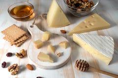 Verschillende soorten kazen op witte houten raad met noten stock foto
