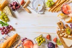 Verschillende soorten kazen, wijn, en snacks op het houten wit stock foto