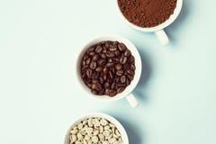 Verschillende types van koffiedik, korrel en niet geroosterd op blauwe pastelkleurachtergrond royalty-vrije stock afbeeldingen