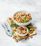 Verschillende types van noten in kommen met groene bladeren royalty-vrije stock afbeelding