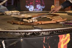 Verschillende types van worsten op een grote grill stock afbeelding