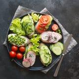 Verschillende veganistsandwiches met groenten, radijs, tomaat, roggebrood op zwarte Voorgerecht voor partij stock foto