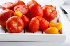 Verschillende verscheidenheden van tomaten op een wit dienblad Kleurrijke rode en gele verse rijpe tomaten stock foto's