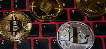 Verschillende virtuele monetaire phisical muntstukken op toetsenbord, bitcoin, litecoin, ethereum en rimpeling stock fotografie