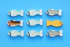 verschillende vissen die tegenover manier van identieke degenen zwemmen Moed en succesconcept stock foto