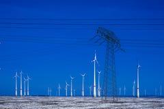 Verschillende windmolens met de transmissielijn van de machtspool in de winterlandschap Stock Fotografie