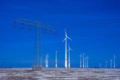 Verschillende windmolens met de transmissielijn van de machtspool in de winterlandschap Royalty-vrije Stock Foto