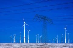 Verschillende windmolens met de transmissielijn van de machtspool in de winterlandschap Royalty-vrije Stock Foto's