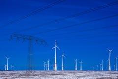 Verschillende windmolens met de transmissielijn van de machtspool in de winterlandschap Stock Afbeeldingen