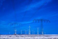 Verschillende windmolens met de transmissielijn van machtspolen in de winterlandschap Stock Afbeeldingen