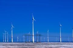 Verschillende windmolens met transmissielijn in de winterlandschap Stock Foto's