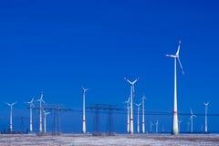 Verschillende windmolens met transmissielijn in de winterlandschap Royalty-vrije Stock Afbeeldingen